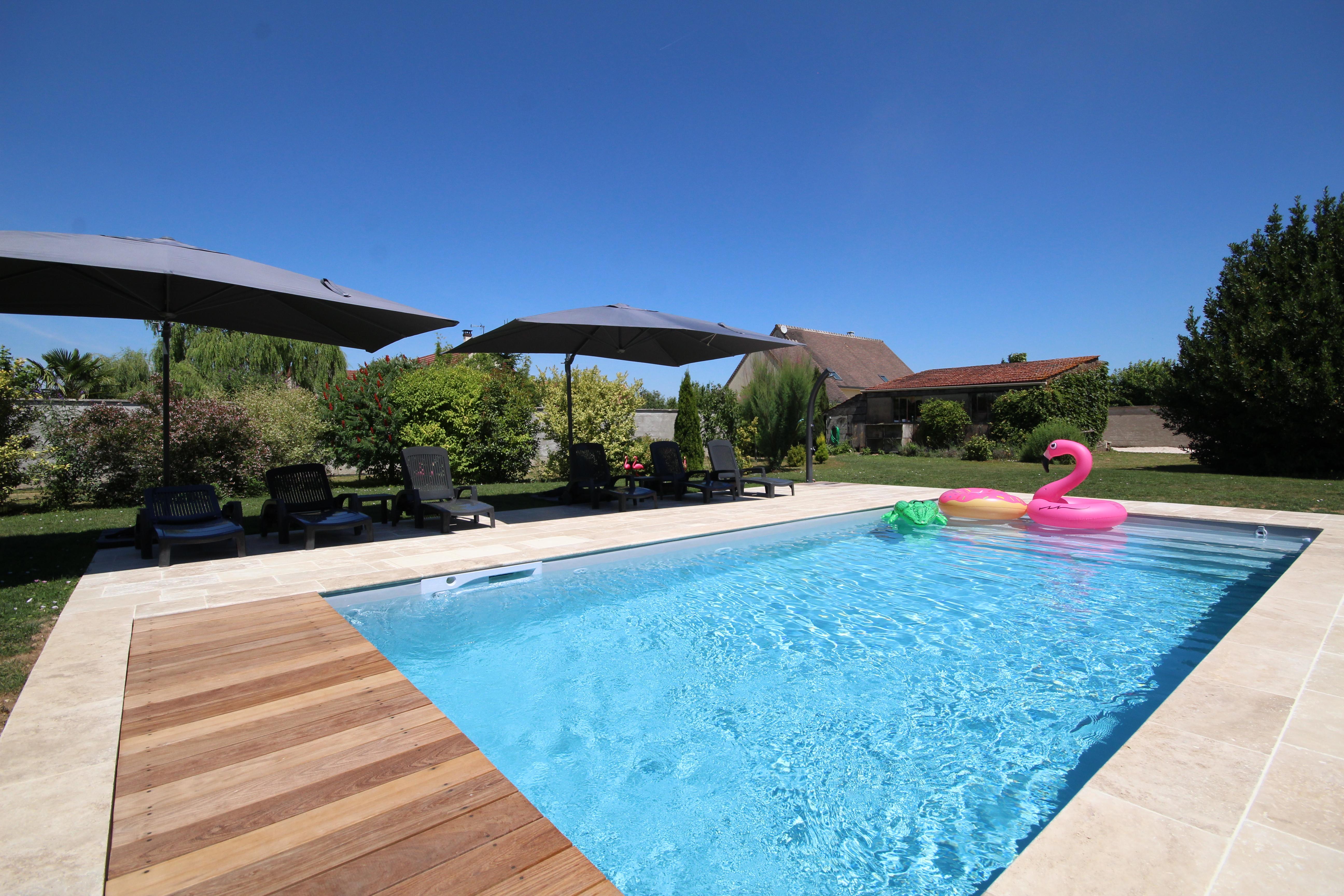 La terrasse en pierre de la piscine est équipé de parasols et transats.