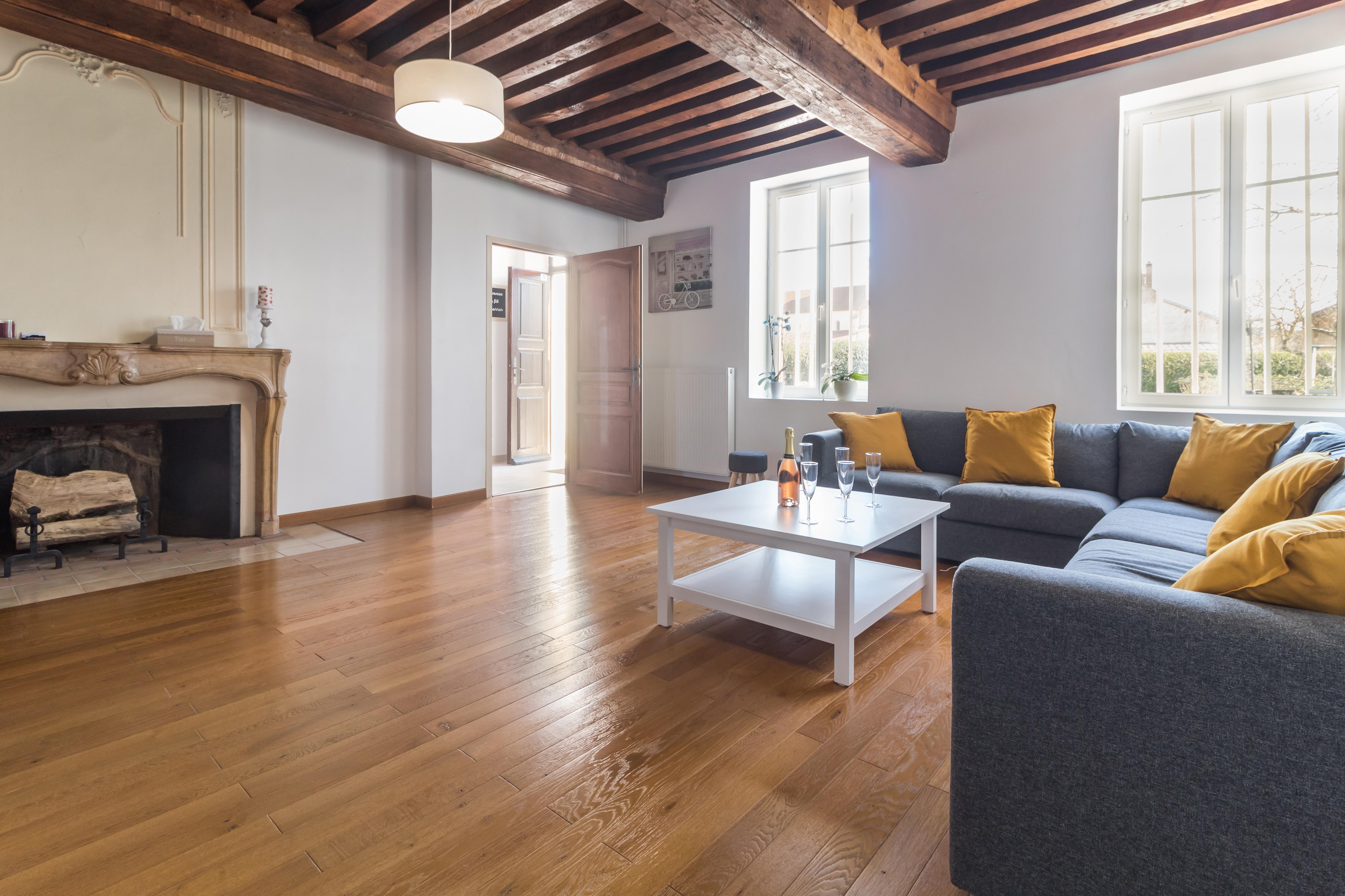 Un grand salon, avec plafond à la française, cheminée en marbre ( non fonctionnelle) et parquet au sol