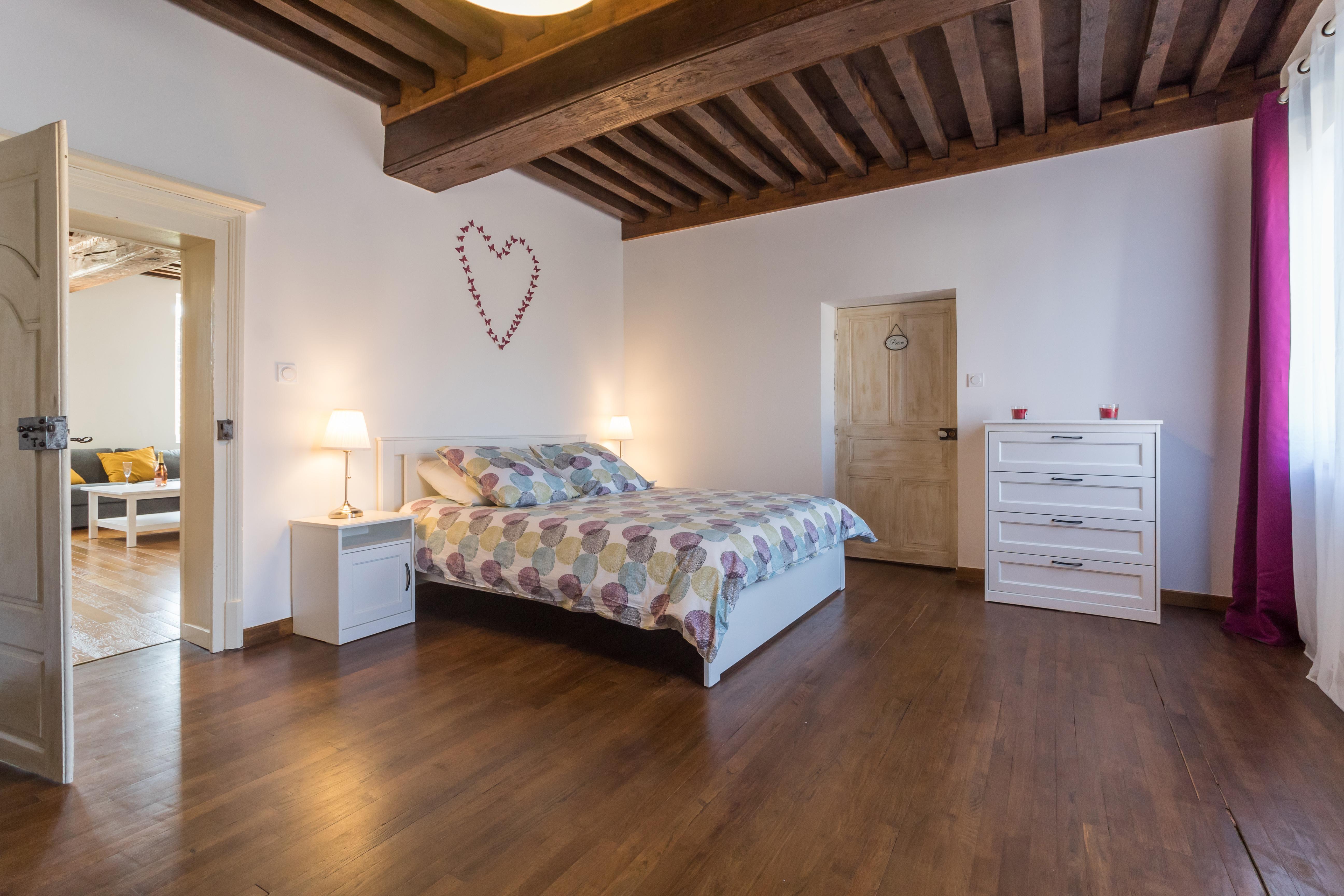 Une très grande chambre avec une cheminée en marbre, des plafonds à la française et un magnifique parquet en chêne